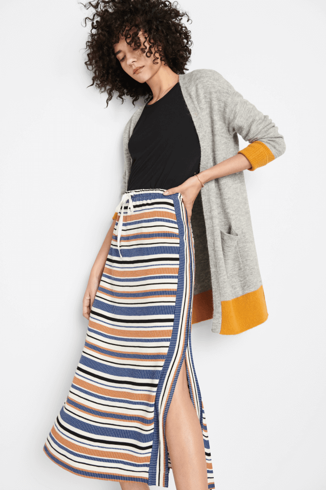 model wearing a long stripped skirt, black top and grey sweater, and Mohnton Made sweatshirt.