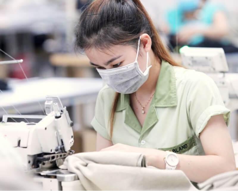 Masked employee sewing.