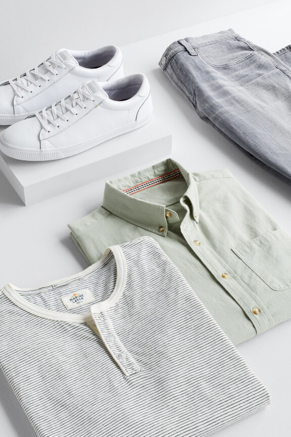 Folded mens green button down and grey crew neck shirt with white casual shoes and grey jeans.