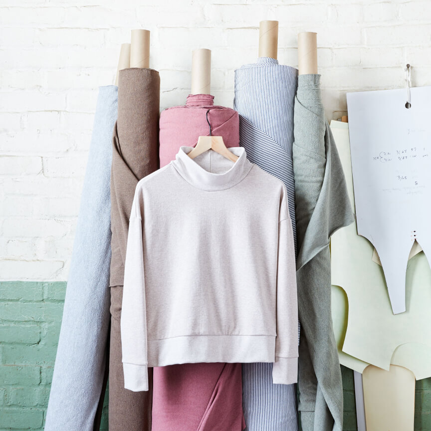 Rolls of fabric leaning on a green and white wall with a beige long sleeve shirt on a hanger.