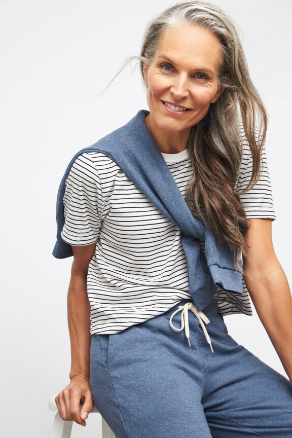 Women's model wearing blue joggers, stripped shirt and blue sweater tied around the shoulders.