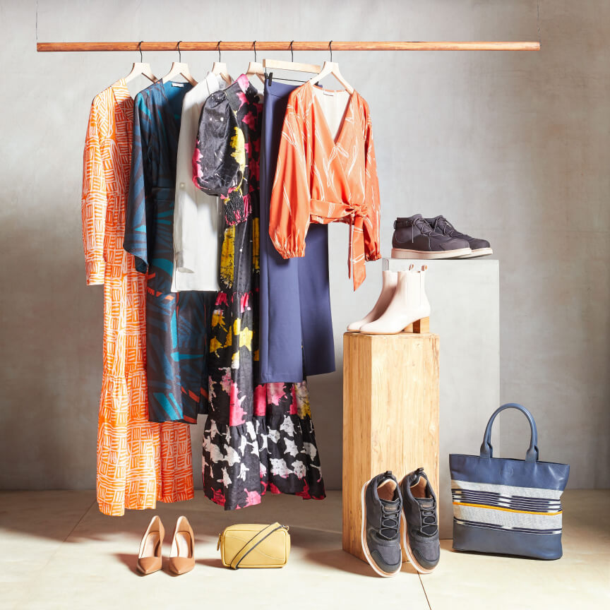 Stitch Fix Elevate grantees clothes hanging on a rack, including blue handbag, black shoes and yellow purse.