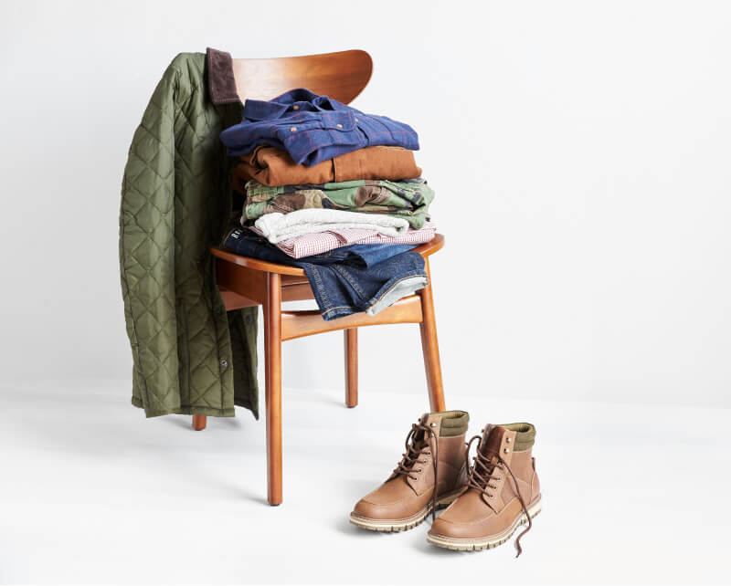 Stack of clothing on chair with green jacket and brown lace-up boots. FILE NAME: stitch-fix-clothing