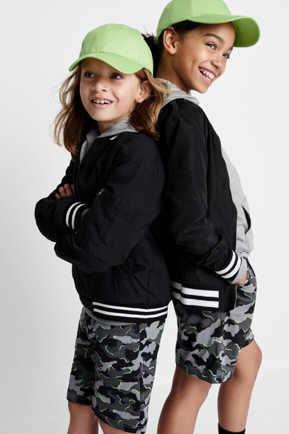 Kid models wearing matching black and grey camo cargo shorts, black varsity jackets and lime green hats.